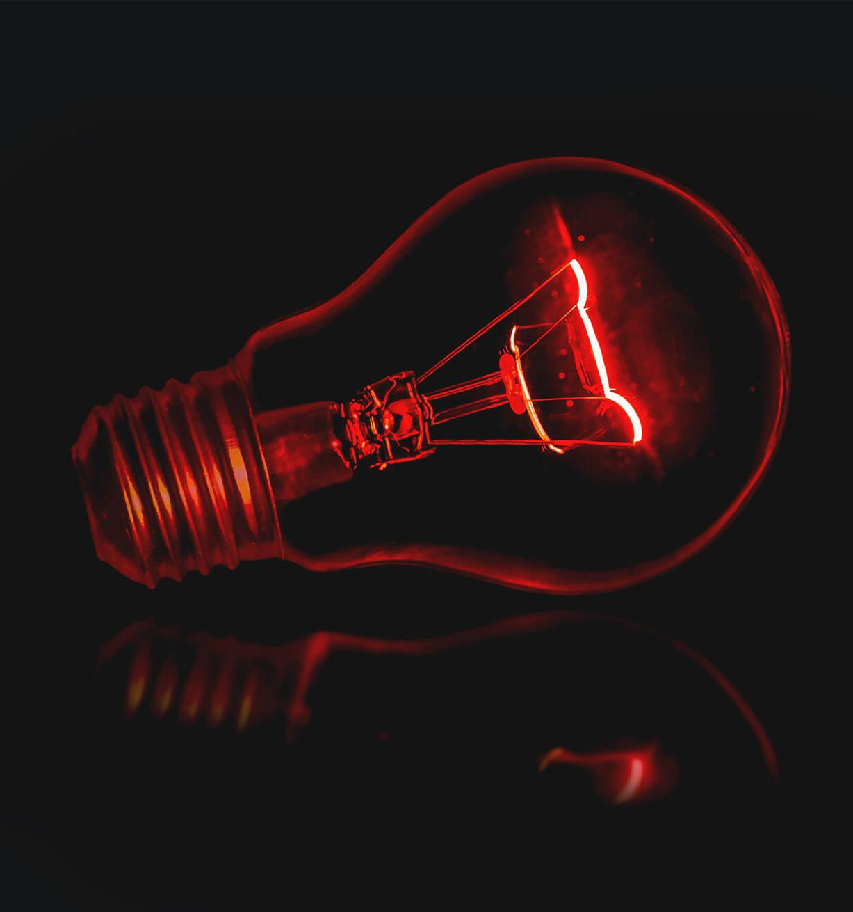 Red enlightened light bulb in front of dark background